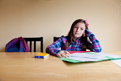 Portrait of girl studying while sitting on table against wall at home - p1166m969180f by Cavan Images