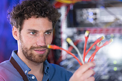 Male IT technician looking at patch cord cables in data center - p300m2275203 by Florian Küttler