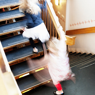Girls running on stairs - p312m1054646f by Susanne Kronholm
