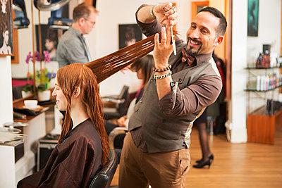 Female customer having long red hair trimmed in hair salon - p429m1407993 by Nancy Honey