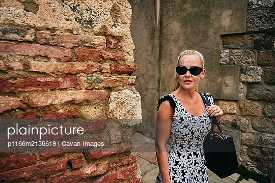 Woman standing at corner of bricked wall in old town - p1166m2136619 by Cavan Images