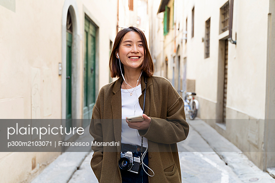 Italy, Florence, happy young woman with earphones and cell phone in an alley - p300m2103071 von Francesco Morandini