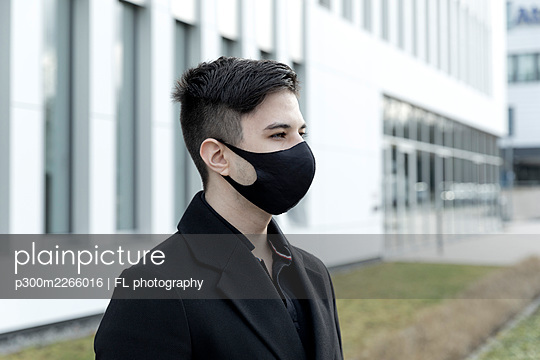 Young male entrepreneur in protective face mask against office building - p300m2266016 by FL photography