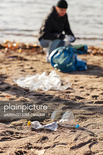 Young environmentalist collecting plastic waste by lake - p426m2213282 by Maskot