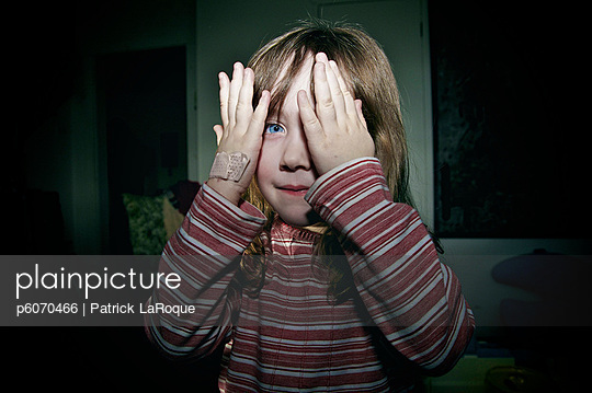 Young girl with bandage on hand playing peek-a-boo, Maricourt, Quebec - p6070466 by Patrick LaRoque