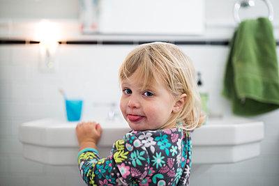 Portrait of baby girl standing by sink in bathroom - p1166m1210815 by Cavan Images
