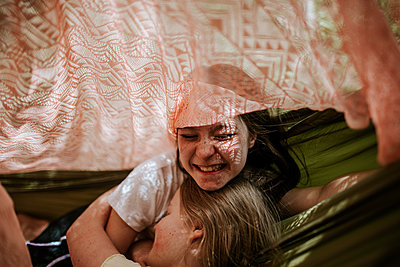 Teen girls laughing and hugging in tent - p1166m2201613 by Cavan Images