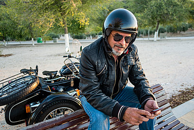 Portrait of biker wearing helmet and sunglasses sitting on backrest of a bench with smartphone - p300m1191793 by Jaen Stock