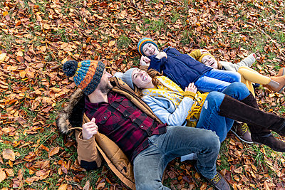 Happy family playing while lying on leaves in forest - p300m2257464 by William Perugini