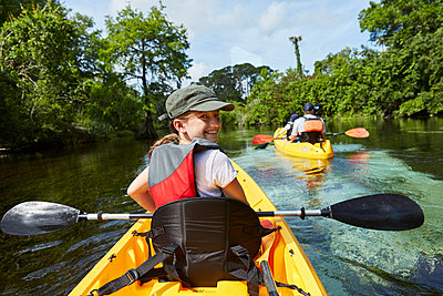 Smiling girl canoeing in lake during vacations - p300m2273672 by Stefanie Aumiller