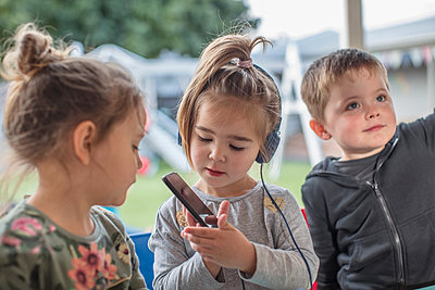 Young girl with friends, using smartphone, wearing headphones - p924m1513559 by Zero Creatives