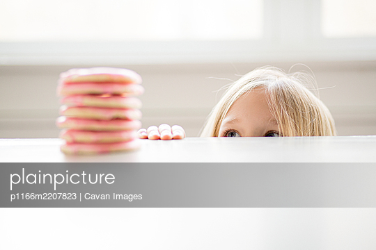 Blond girl peeking at stack of pink frosted sugar cookies on table - p1166m2207823 by Cavan Images