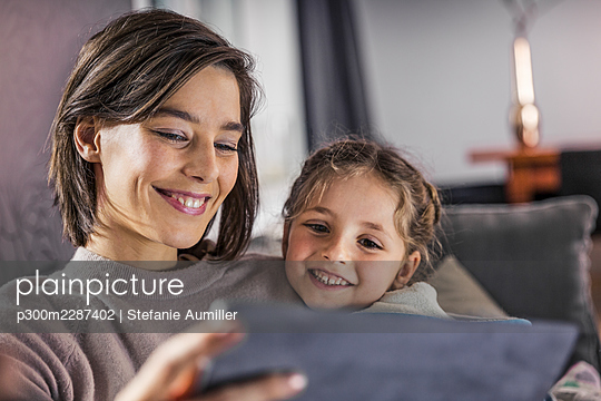 Smiling mother and daughter using digital tablet at home - p300m2287402 by Stefanie Aumiller