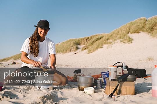 Smiling woman cooking on beach - p312m2217243 by Stina Gränfors