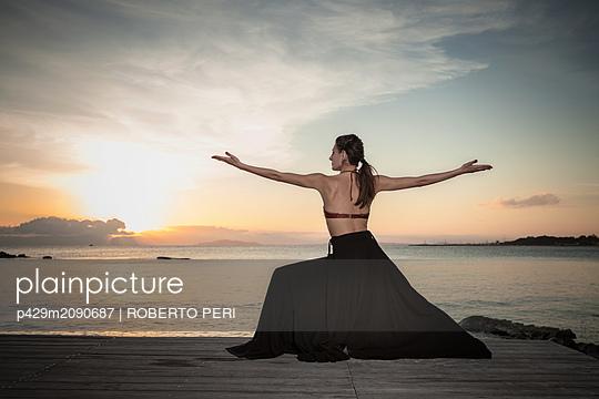 Woman practising yoga at seaside - p429m2090687 by ROBERTO PERI