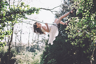 Little girl swinging - p1150m1041224 by Elise Ortiou Campion