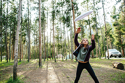 Girl catching plastic disc while standing in forest - p1166m2034961 by Cavan Images