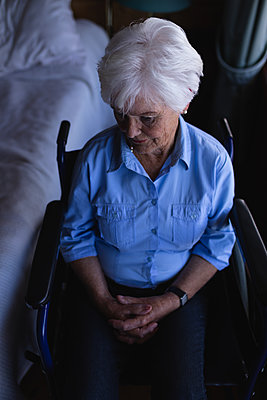 Disabled active senior woman with hand clasped sitting on wheelchair in bedroom at home - p1315m2091076 by Wavebreak