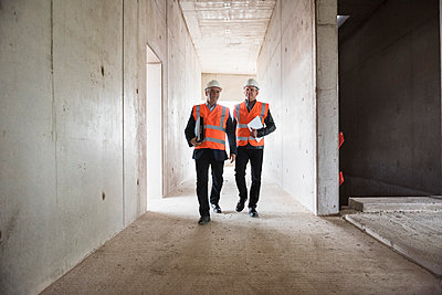 Two men wearing safety walking in building under construction - p300m1460686 by Daniel Ingold
