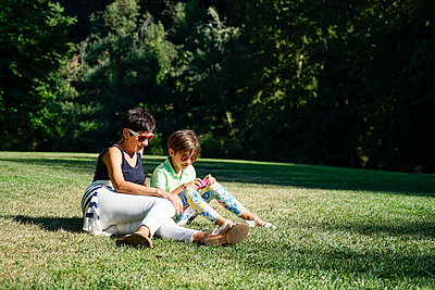 Mother and daughter taking photographs, sitting on grass - p300m2029465 von Javier Sánchez Mingorance