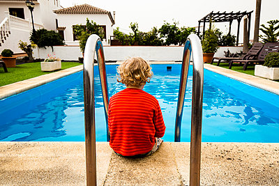 Back view of little boy sitting in front of a swimming pool - p300m2180847 by Irina Heß