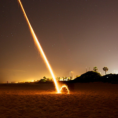 A firework exploding on a beach at night - p301m960852f by Peter Baker