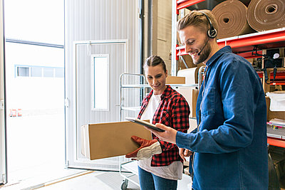 Smiling man showing digital tablet to female coworker holding box in distribution warehouse - p426m1580261 by Kentaroo Tryman