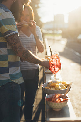 Couple eating tapas at sunlit sidewalk cafe - p429m1494261 by Eugenio Marongiu