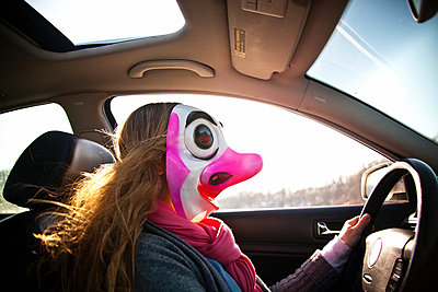 Woman driving car wearing clown mask - p9240646 by Adam Hester