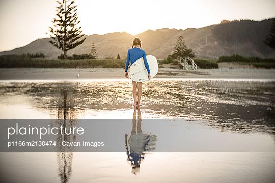 Tween girl on New Zealand beach holding surfboard - p1166m2130474 by Cavan Images