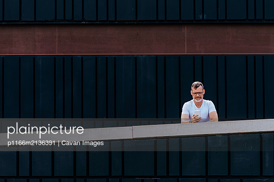 Mature bearded man using a mobile phone leaning on a fence - p1166m2136391 by Cavan Images