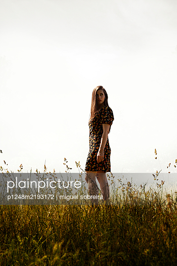 Woman in summer dress in the meadow - p1248m2193172 by miguel sobreira