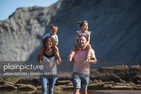 Parents carrying children on shoulder while walking at beach - p300m2257253 by SERGIO NIEVAS
