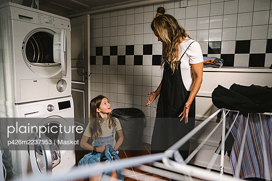 Mother and daughter doing laundry in utility room - p426m2237953 by Maskot