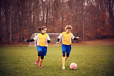 Happy soccer players playing on field against trees - p1166m1038256f by Cavan Images