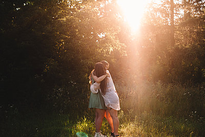 Happy girlfriends embracing in forest during summer - p1166m2212453 by Cavan Images