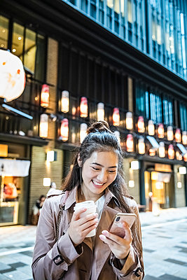 Happy young woman holding takeaway drink and using smartphone in Ginza, Tokyo, Japan - p300m2140607 by 27exp