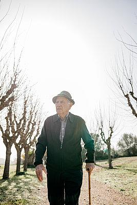 Spain, Barcelona. Retired senior man walking through a park in winter with his cane - p300m2167178 von Josep Rovirosa