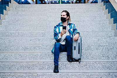 Man wearing protective face mask using mobile phone while sitting with luggage on steps - p300m2242369 by Eva Blanco