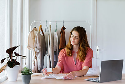 Female fashion designer reading price tag while sitting by laptop at home - p300m2287126 by VITTA GALLERY
