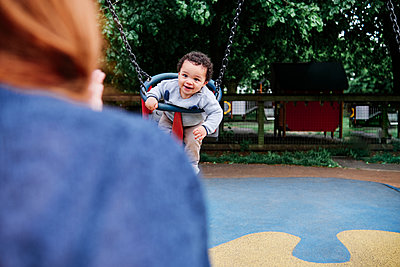 Boy swinging in playground - p300m2287383 by Angel Santana Garcia