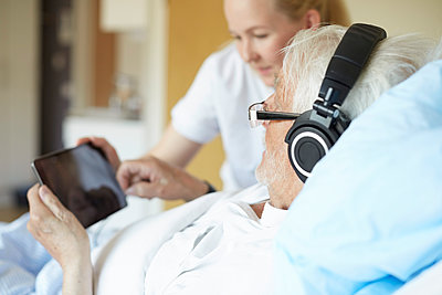 Senior man wearing headphones while using digital tablet with female nurse on hospital bed - p426m1494057 by Maskot