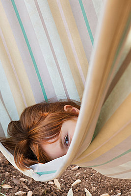 Young girl looking out from a hammock - p429m1450323 by Axel Bernstorff