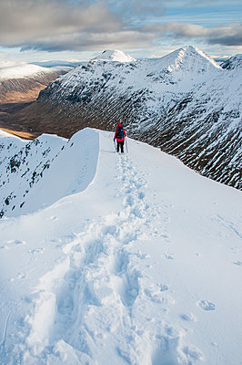 A female walker descending from the summit of Stob Dubh on Buchaille Etive Beag on a crisp winter day, Highlands, Scotland, United Kingdom - p871m2057970 by George Robertson