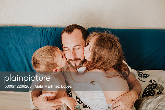 Daughter and son kissing father on cheek in bedroom at home - p300m2266265 by Gala Martínez López