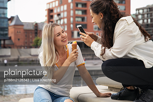 Two young women eating ice cream - p788m2128343 by Lisa Krechting