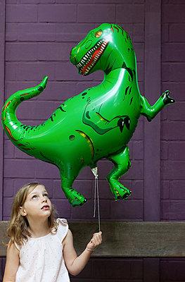 Mädchen mit großem Dinosaurier-Luftballon - p045m1181838 von Jasmin Sander