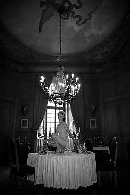 Woman in vintage lingerie on a table in a castle - p1521m2214977 by Charlotte Zobel