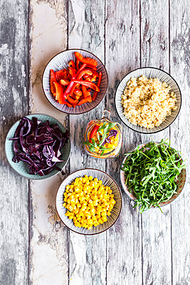 Glass of rainbow salad with bulgur, rocket and different vegetables and bowls with ingredients - p300m1356344 by Sandra Roesch