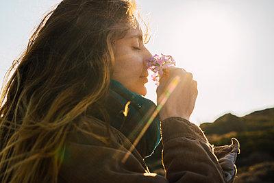 Woman in sunlight enjoying fragrance of a flower - p300m1581185 by Kike Arnaiz